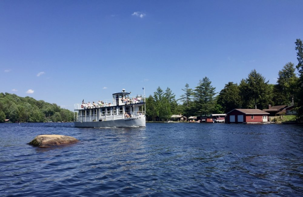 A barge on the lake with people sitting on the top and bottom deck enjoying the sun