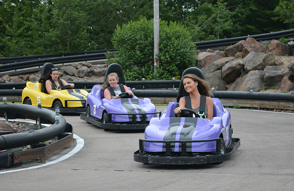 Three girls smiling and racing on go-karts