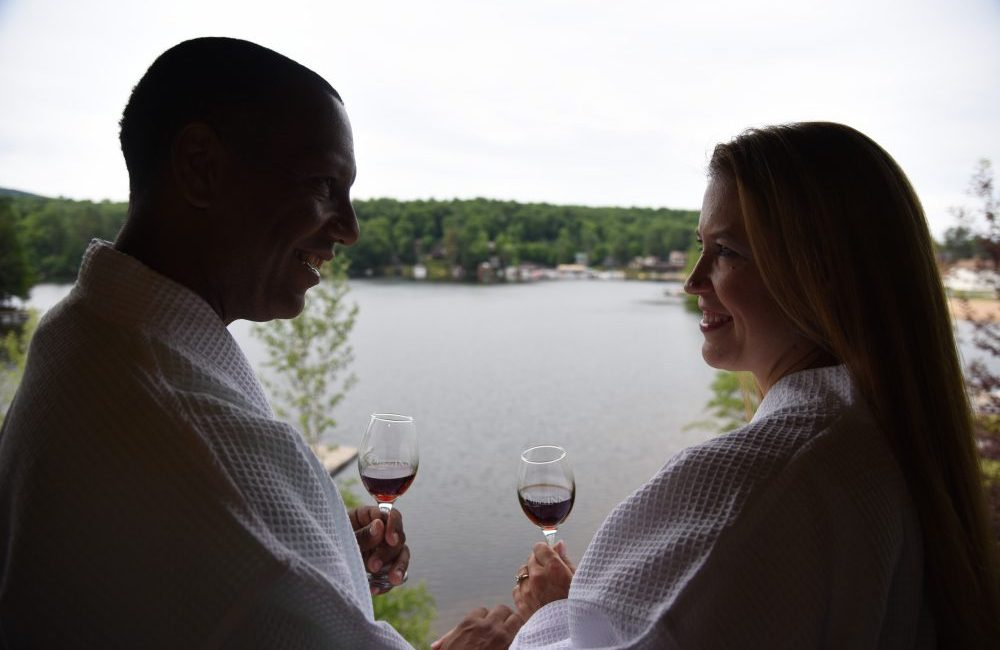 A couple in bathrobes on a porch sipping wine with the lake in the background