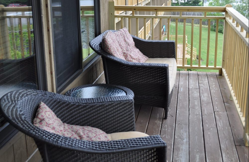 Two wicker chairs with cushions on a porch facing the lake
