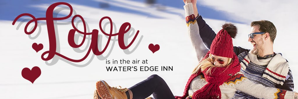 A couple on a sled laughing with love is in the air at water's edge in written next to them