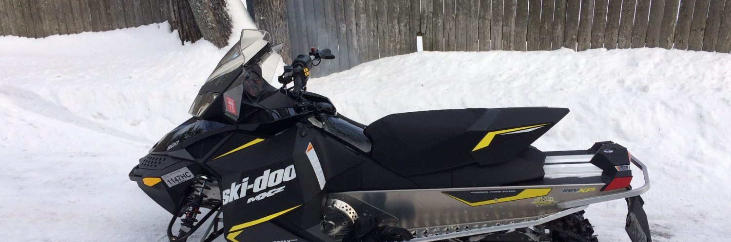 A ski-doo snowmobile parked in the snow