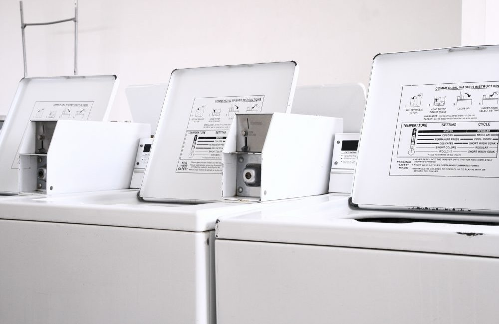 Three white coin operated washing machines