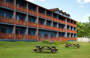 Waters edge inn from the outside, its a wooden building with blue painted walls on the porches and Adirondack chairs outside of every room and two picnic tables outside