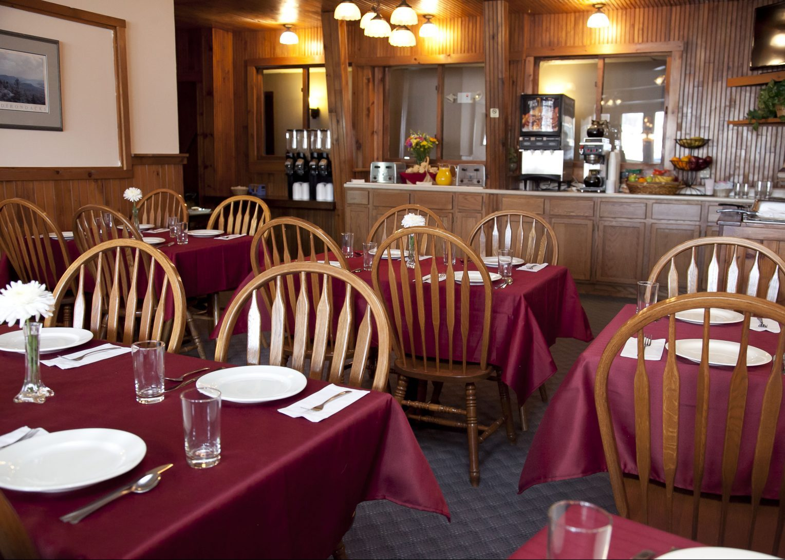 A restaurant with maroon table cloths a centerpiece of a large white flower, wooden chairs and place settings set at each table