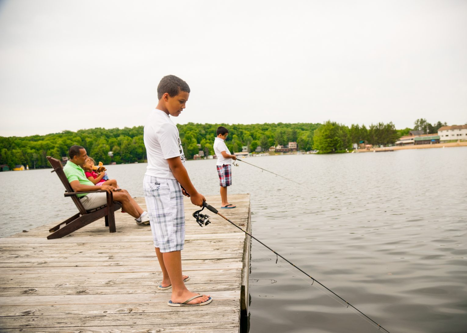 A family on a dock with the two boys fishing