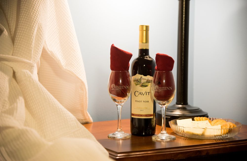 A bedside table with a plate of cheese and crackers and a bottle of wine as well as two wine glasses with napkins nicely placed in the glasses
