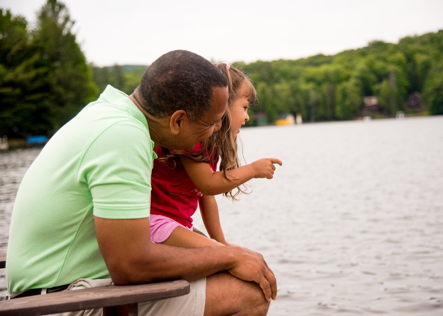A dad and his daughter sitting in an Adirondack chair on a dock smiling out at the lake on a summer day