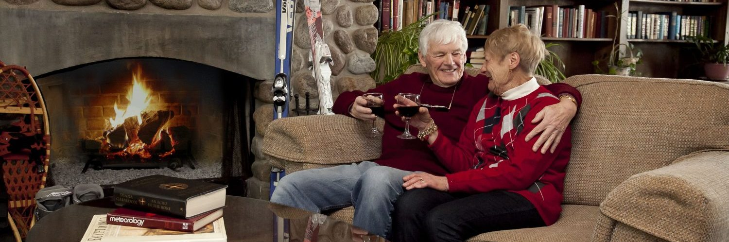 An old couple sitting together on a couch by a roaring fireplace, smiling at each other with wine glasses in their hands