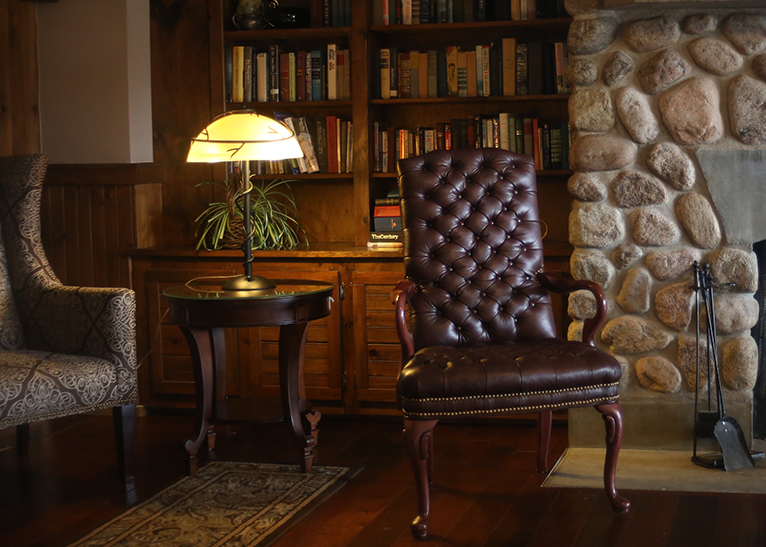 A beautiful leather chair sitting next to a stone fireplace, behind the chair are wooden build in shelves filled with books and next to the chair is a table with a lamp on it