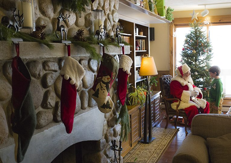 A fireplace decorated for Christmas with stockings hanging from it and next to the fireplace is Santa sitting in a chair talking to a little boy, and behind them is a decorated Christmas tree