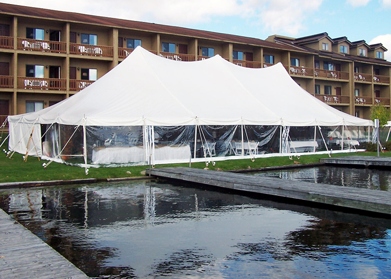 The outside of Water's Edge Inn is a big white tend with chairs and tables set up inside and next to the tent are docks on the lake