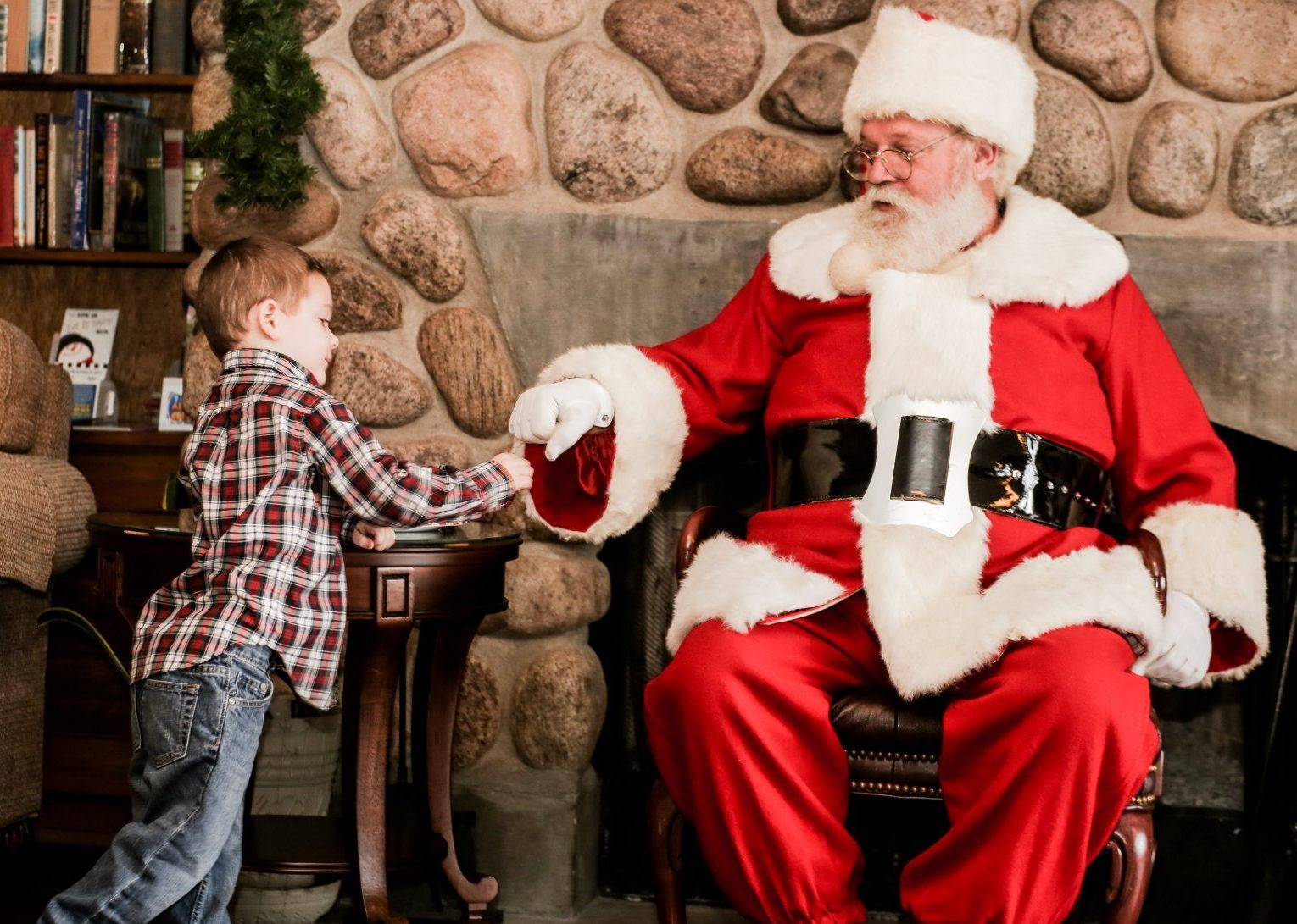Santa in front of a stone fireplace fist bumping a little boy