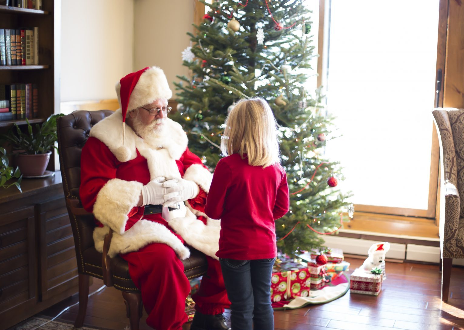 Santa next to a Christmas tree talking to a little girl