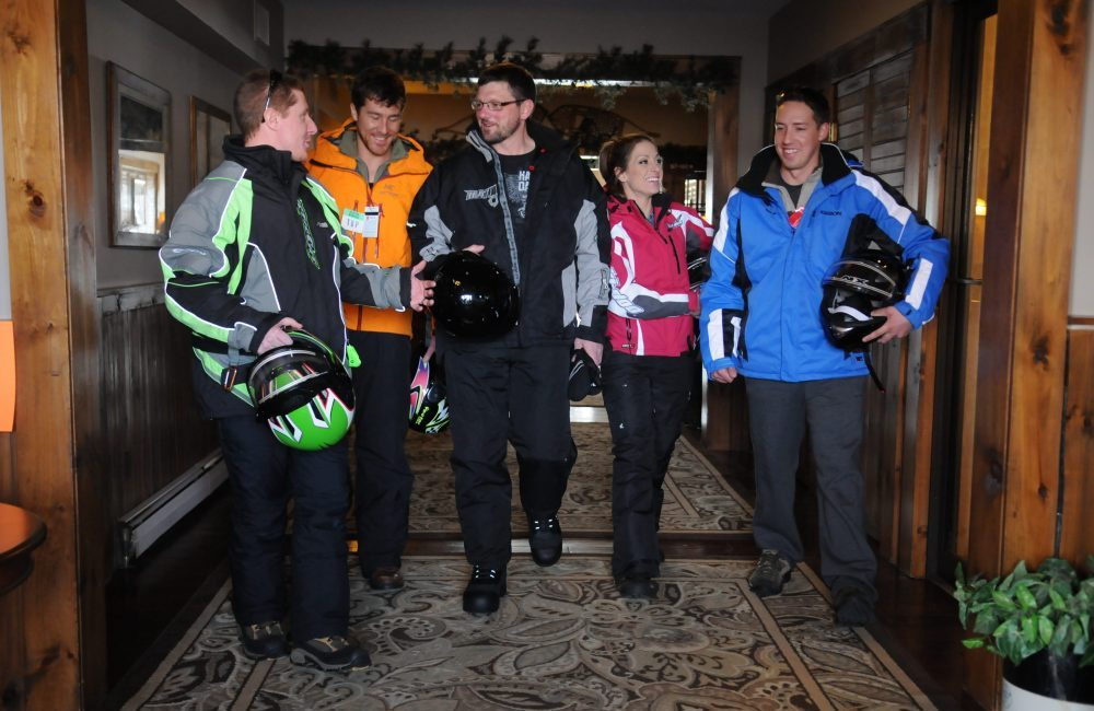 Five people in their winter gear holding snowmobiling helmets talking inside