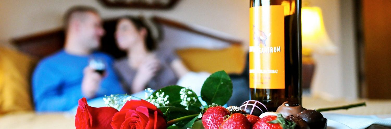 An image of a couple smiling at each other sitting on a bed with wine glasses in their hands in the forefront of the photo there are two roses, a plate oof strawberries and chocolate and a bottle of wine