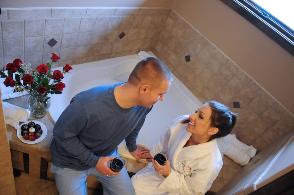 A couple sitting on the side of the bathtub drinking wine and smiling next to them is a plate of chocolates and strawberries and a vase of roses