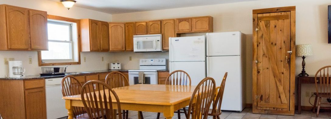 Demonstrating the kitchen and dining area in one of the vacation rentals.