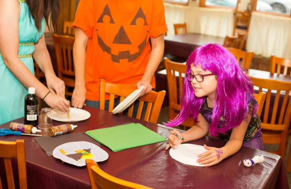 A little girl in a halloween costume doing crafts