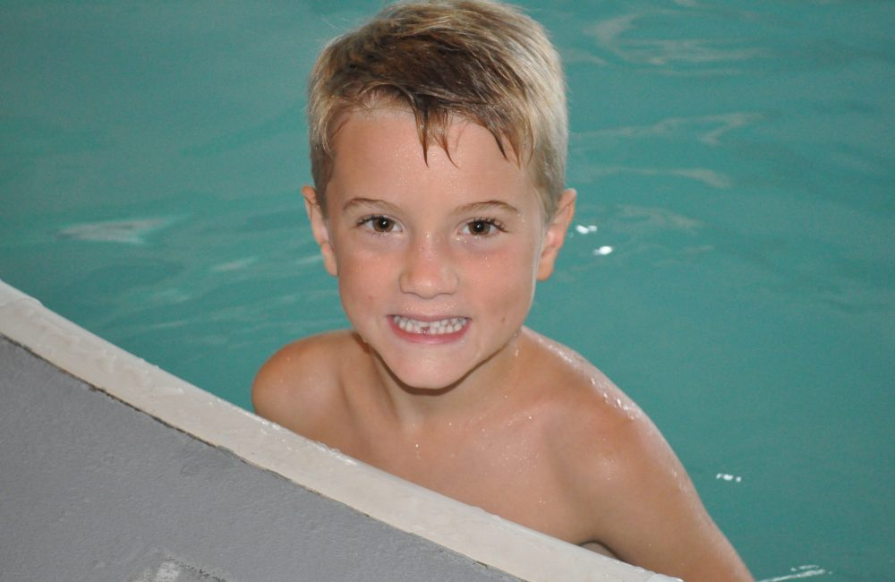 A boy in the pool on the edge smiling