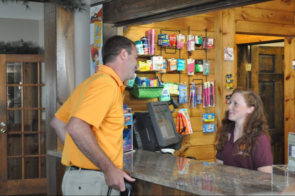 A man speaking to a friendly cashier