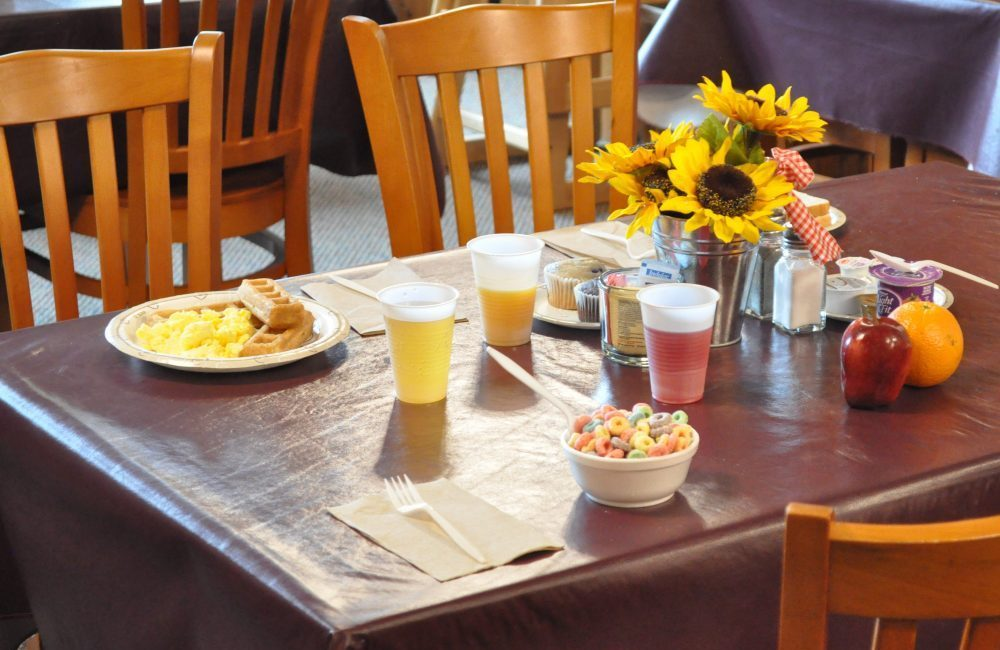 A table with a maroon table cloth and wooden chairs around it on the table are sunflowers as a centerpiece and breakfast set out