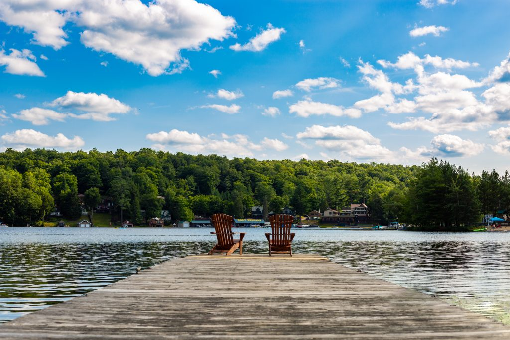 A dock facing the clam lake and green trees on the other side on the dock there are two Adirondack chairs