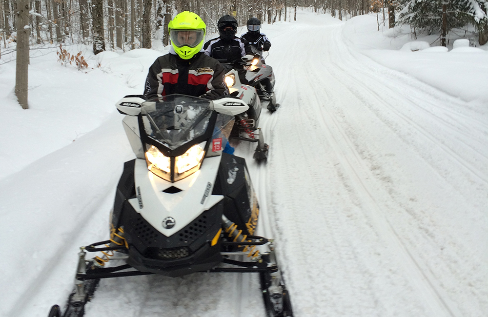 Three people on snowmobiling on a trail