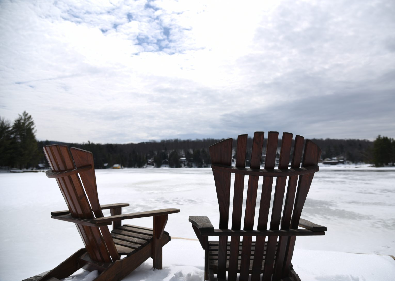 Two Adirondack chairs facing the frozen lake