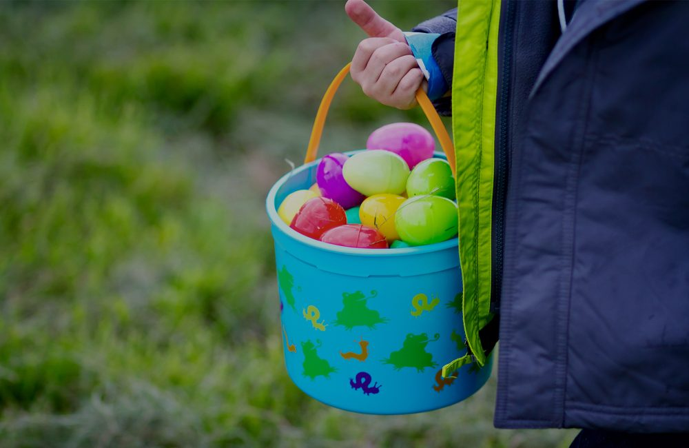 A kids hand holding a blue easter basket full of colorful plastic eggs
