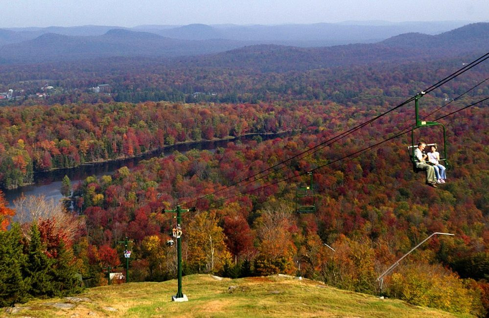 A father and daughter on a chairlift in the fall with the Adirondack mountains and a lake behind them