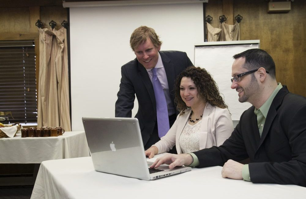 Three business people looking at a laptop in a conference room
