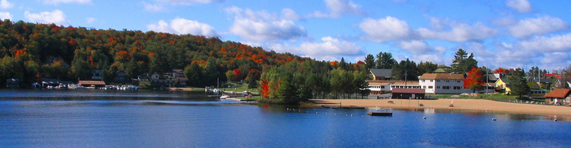 View from the docks of the blue lake and the tree line half green from pine trees and half red with fall foliage