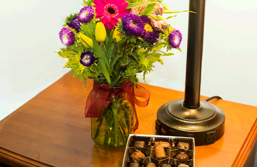Vase of flowers and chocolate on a nightstand