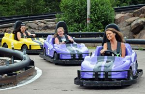 Three girls smiling and racing on go karts