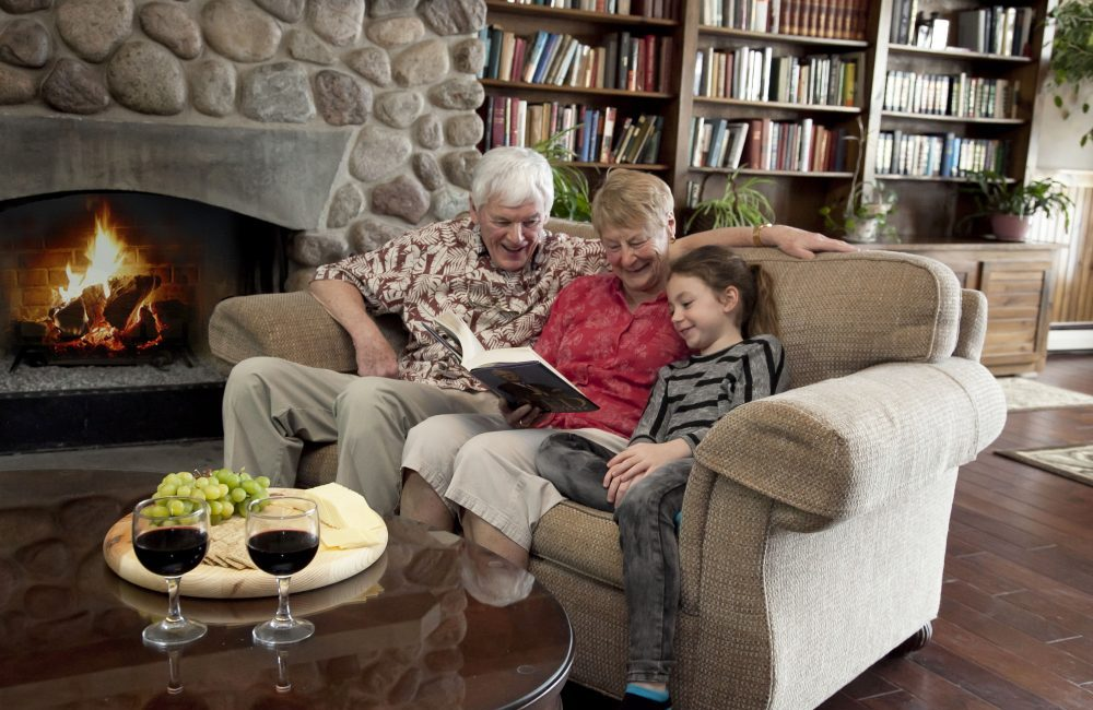 An older couple reading to their granddaughter by a roaring fire