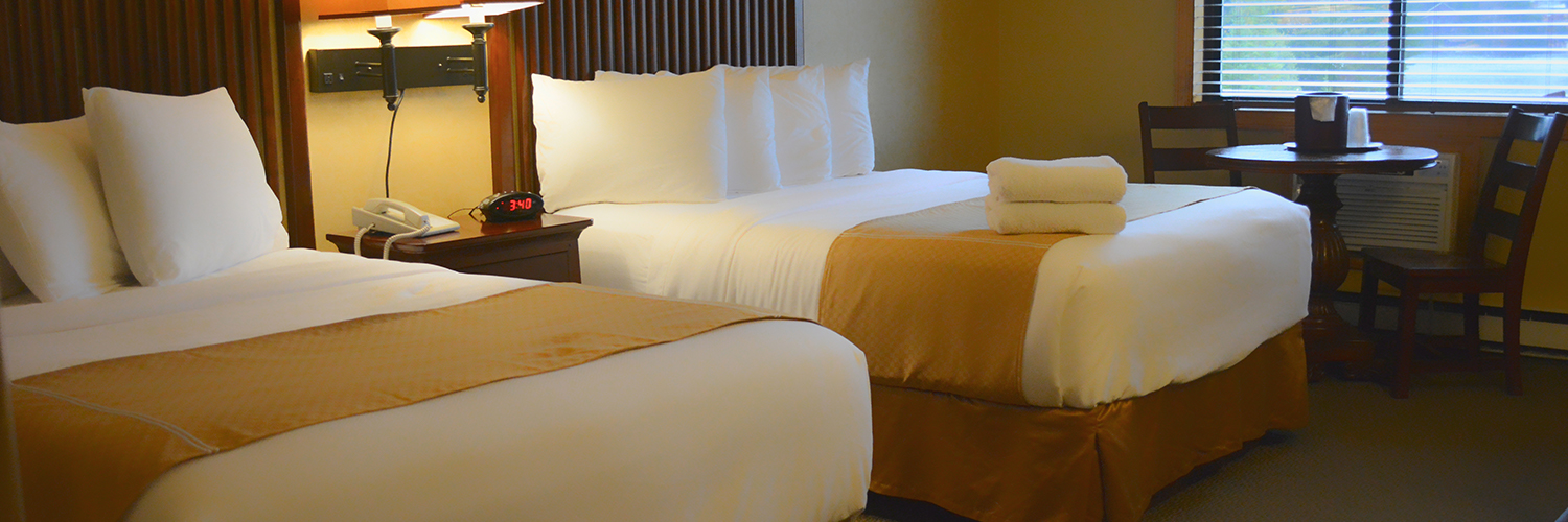 A hotel room with two beds with a nightstand between them and a small table with two chairs set up beneath a window