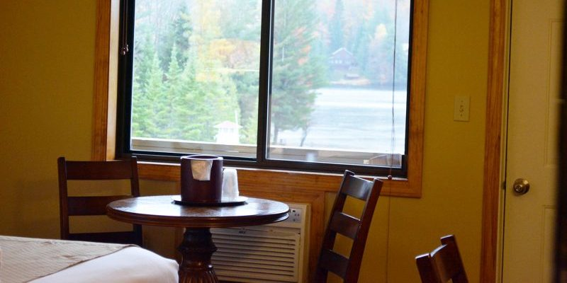 A small table with two chairs next too a window with a lake view