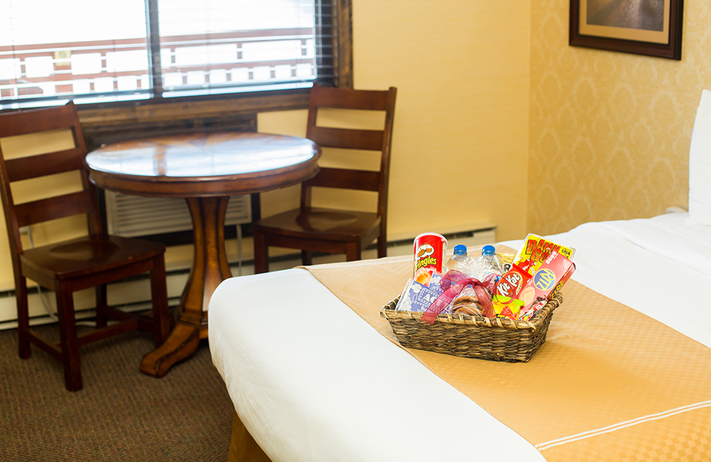 A hotel room bed with a movie night basket goodies on it