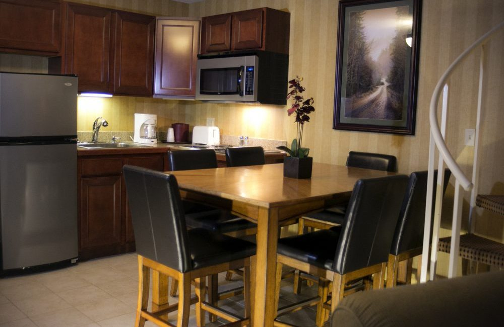A kitchen with wooden cabinets, stainless steel appliances, a wooden table with flowers on it a wood and leather chairs around it