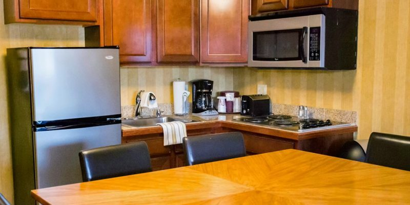 A kitchen with a fridge, sink, microwave, stove, coffee maker, toaster, wooden cabinets, and a wooden table