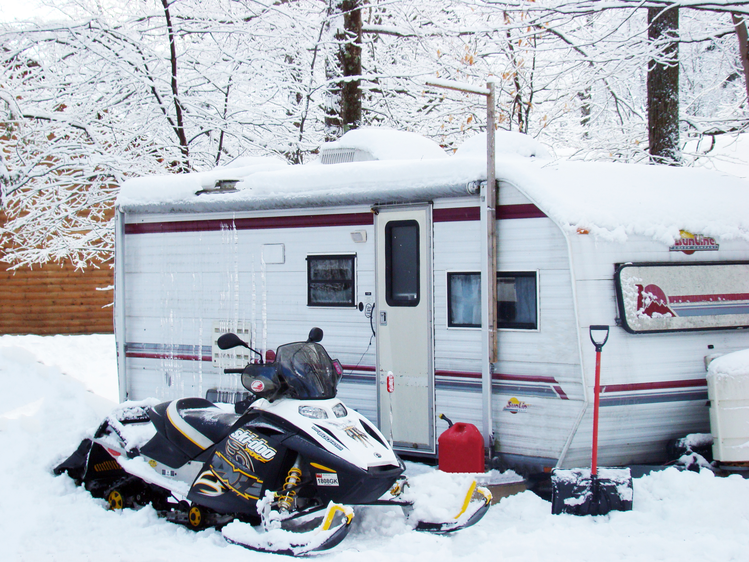 A camper and a snowmobile in winter