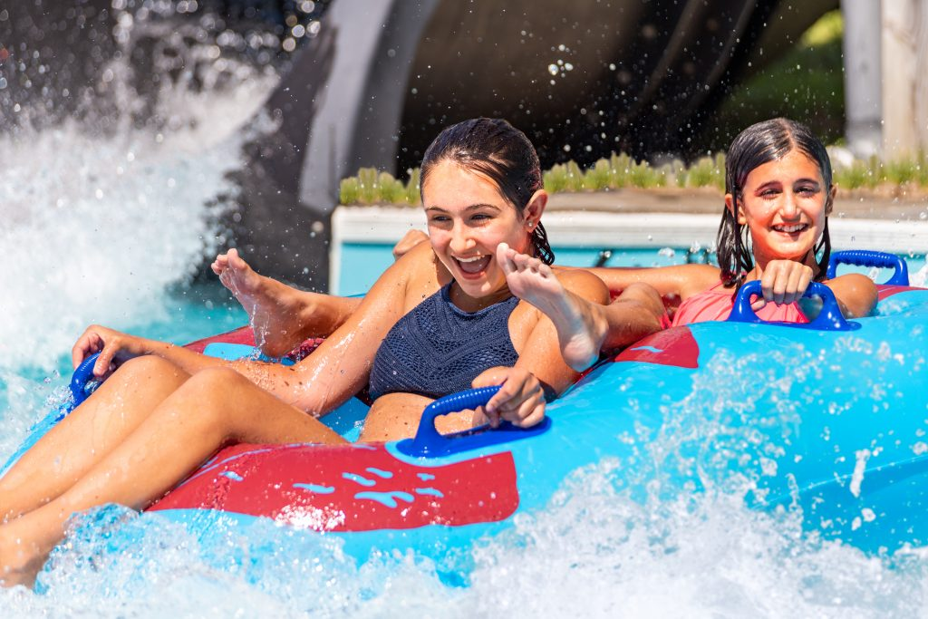 Two girls in a double float smiling as water splashes around them