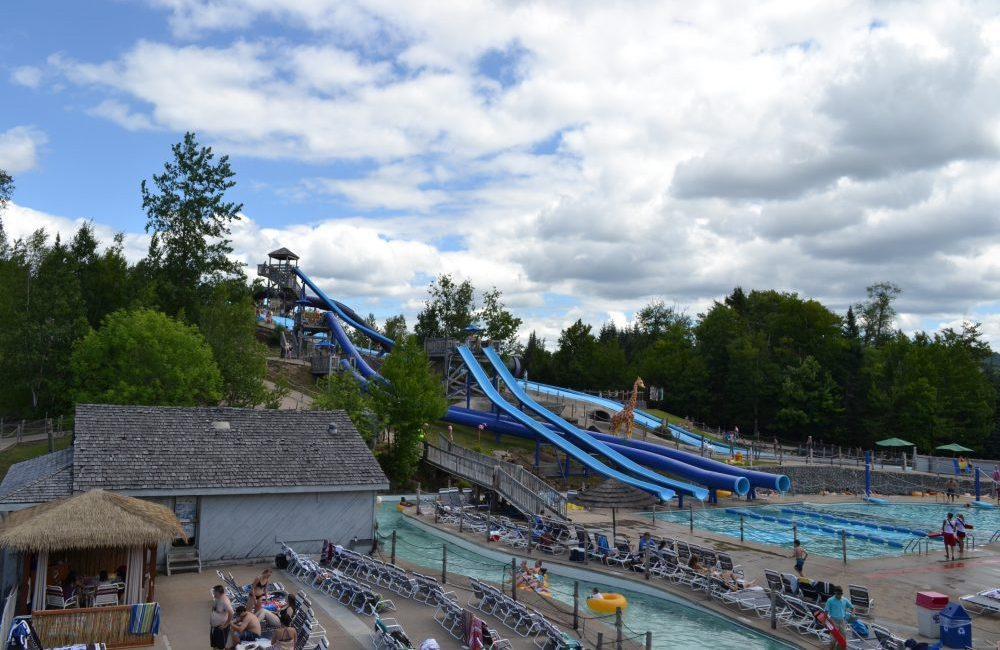 Large water slides, pools, and pool chairs with people walking around at water safari