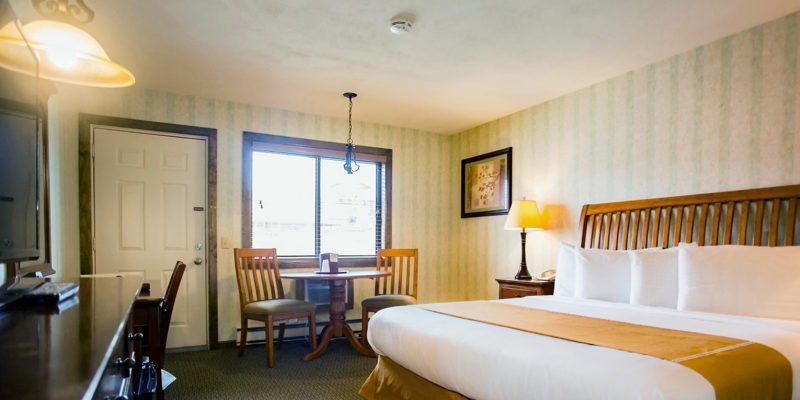 A hotel room with a king size bed as well as a dresser with a flat screen tv and to the side of the room is a window with a small table and two chairs set up beneath it