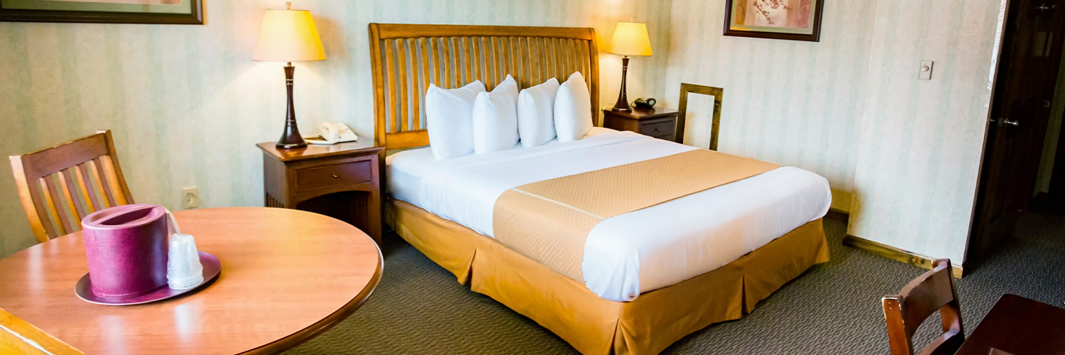 A hotel room with a king bed, two nightstands, and a small table and chairs