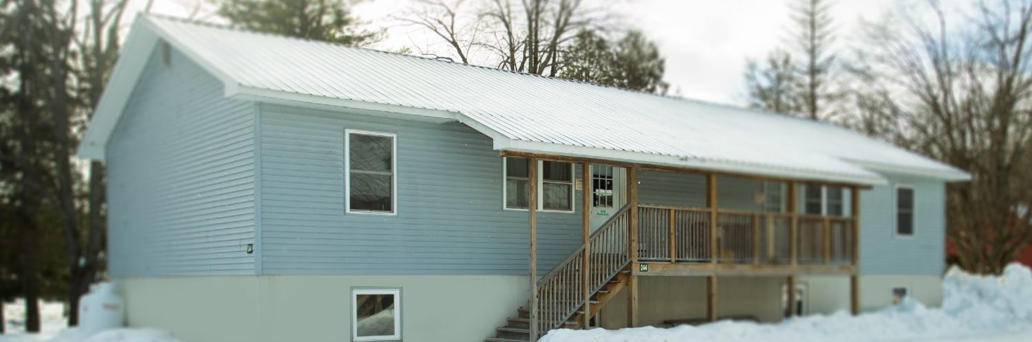 A grey house ing winter with a wooden porch