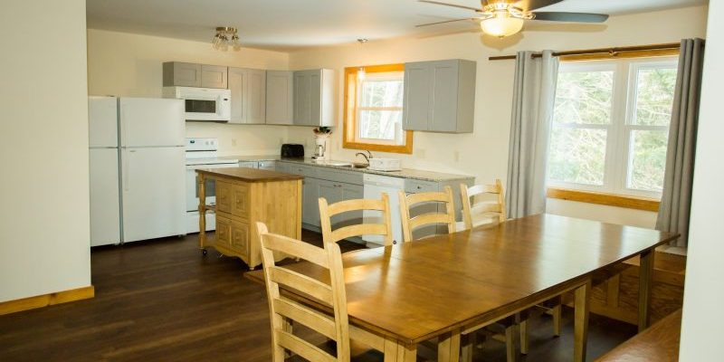 A kitchen with full appliances and a long wooden dining room table