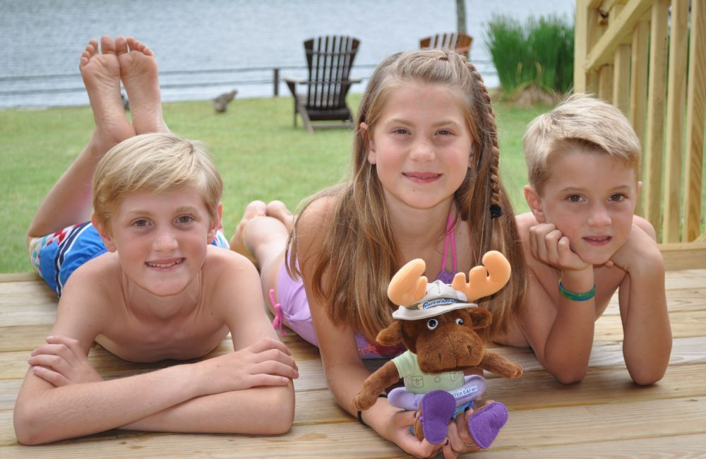 Three kids on a porch in front of the lake in their bath suits and a stuffed Walter Safari