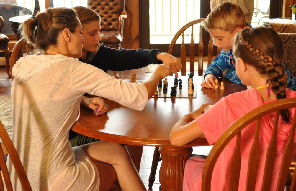 a family at the table and the kids are playing chess